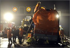 Firefighter work on a bus with blankets, which was burned out on the motorway near Hannover Garbsen, Germany on late Tuesday, Nov. 4, 2008. A tour bus returning from a day trip to a farm caught fire on a highway near the northern German city of Hannover on Tuesday night, killing 20 people, after a passenger reportedly sneaked a cigarette, police said.  (AP Photo/Fabian Bimmer)
