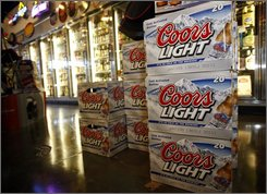 Packages of Coors Light are on display in front of coolers in a liquor store in southeast Denver on Monday, Nov. 3, 2008. Brewer Molson Coors said Wednesday, its third-quarter profit rose 28 percent, but that result missed analysts' expectations. (AP Photo/David Zalubowski)