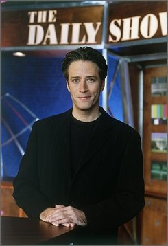 """Jon Stewart, new host of """"The Daily Show"""" on Comedy Central, poses on the parody newscast's set in this 1999 file photo. Culminating their satirical coverage of the campaign Tuesday Nov. 4, 2008 , Comedy Central's Jon Stewart and Stephen Colbert teamed up for a live one-hour comedy special -- though Stewart had his Cronkite moment, too. About 11 p.m. EST, Stewart became possibly the first comedian to announce presidential election result on live national television. (AP Photo/Frank Micelotta/Comedy Central)"""
