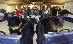 Voters huddle over booths as others fill the area behind waiting shortly after the polls opened in the basement of the Greenwood Christian Church Tuesday, Nov. 4, 2008, in Seattle. (AP Photo/Elaine Thompson)
