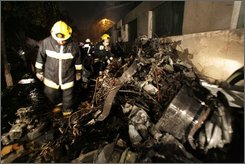 Firefighters walk next to aircraft parts after a small airplane crashed during rush hour in Mexico City, Tuesday Nov. 4, 2008. The plane plane crashed in a wealthy Mexico City neighborhood, killing the nation's Interior Secretary Juan Camilo Mourino and at least seven others, and setting dozens of cars ablaze. (AP Photo/Eugenio Gomez)