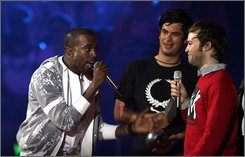 "In this Thursday Nov. 2, 2006 file photo, Kanye West, left, complains alongside  Jeremie Rozan and Martial Schmeltz, directors of the video for ""We Are Your Friends"" by Justice Vs Simian at the MTV Europe Music Awards at The Bella Centre, Copenhagen, Denmark. When Kanye West performs Thursday, Nov. 6, 2008 at the MTV Europe Music Awards, it will be the second time he's taken the stage at the ceremony -- but the first time he's been invited.  (AP Photo/Jon Super)"