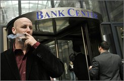  Balazs Ven, a Hungarian broker smokes his cigar in front of the Bank Center in downtown Budapest, Hungary, in this Oct. 29, 2008 file picture.  Hungary's currency and stock market plunged because of the financial crisis, as investors feared Hungary would be unable to make debt payments. The forint temporarily lost some 40 percent of its value against major currencies like the U.S. dollar and the euro while shares on the Budapest Stock Exchange dropped to four-year lows.  (AP Photo/Bela Szandelszky, file)
