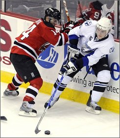 Tampa Bay Lightning's Matt Carle, right, handles the puck as he is checked by New Jersey Devils' Brian Gionta during the first period of an NHL hockey game Wednesday night, Nov. 5, 2008 in Newark, N.J. (AP Photo/Bill Kostroun)