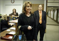 Alaska Gov. Sarah Palin walks into her office in Anchorage, Alaska on Friday Nov. 7, 2008 for the first time since she began campaigning as Sen. John McCain's vice president candidate. Palin's Anchorage Office Director, Kris Perry, left, and Bill McAllister, Communications Director and Press Secretary, right, watch. (AP Photo/Al Grillo)