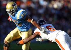 UCLA tailback Kahlil Bell, left, runs for a first down while being tackled by Oregon State's Keenan Lewis during the first half of an NCAA college football game, Saturday, Nov. 8, 2008, in Pasadena, Calif. (AP Photo/Jeff Lewis)
