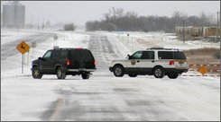 A Highway Patrol officer instructs a vehicle to turn around as it is leaving city limits, Friday, Nov. 7, 2008, in Devils Lake, N.D.  In northeastern North Dakota, the Nodak Rural Electric Cooperative said thousands of rural customers in parts of Grand Forks, Griggs, Ramsey, Steele and Walsh counties were without power early Friday. (AP Photo/Devils Lake Journal,  Sue Kraft Fischer)