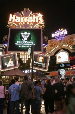 In this April 4, 2007 file photo, travelers crowd an outdoor shopping mall in front of Harrah's hotel-casino in Las Vegas. Harrah's Entertainment Inc. on Friday, Nov. 7, 2008, reported a loss in the third quarter compared to a profit a year earlier, reflecting reduced spending by consumers in its Las Vegas casinos and closing of several Gulf Coast properties during Hurricane Ike.  (AP Photo/Jae C. Hong, file)