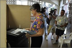 Hawaii Governor Linda Lingle puts her ballot into the tallying machine after casting her votes at McKinley High School in Honolulu, Tuesday, Nov. 4, 2008. (AP photo/Ronen Zilberman)