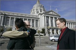 Gay rights activist Stuart Gaffney, left, gets a hug from friend, Patrick Connors, center, as Gaffney's  partner John Lewis, right, looks on outside of City Hall, where Gaffney and Lewis married this past summer, in San Francisco, Wednesday, Nov. 5, 2008. In an election otherwise full of liberal triumphs, the gay rights movement suffered a stunning defeat as California voters approved a ban on same-sex marriages that overrides a recent court decision legalizing them. (AP Photo/Marcio Jose Sanchez)