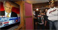 In this Nov. 4, 2008 file photo, Barack Obama supporters at Tacoma's Caballero Club stopped to listen to Republican presidential candidate John McCain's concession speech.  (AP Photo/The News Tribune, Drew Perine, file)