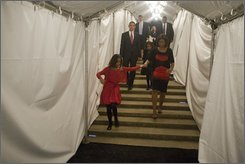 In this photograph released by President-elect Obama, Michelle Obama, wife of then Democratic presidential candidate Sen. Barack Obama, D-Ill., walks with her daughter Malia and others Wednesday, Nov. 5, 2008 in Chicago. (AP Photo/Obama for America, David Katz)