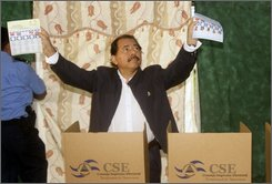 Nicaragua's President Daniel Ortega shows his ballots to reporters before casting them during municipal elections in Managua, Sunday, Nov. 9, 2008. (AP Photo/Arnulfo Franco)