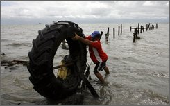 A man pulls a tire out of the water in the aftermath of Hurricane Paloma in Santa Cruz del Sur, Cuba, Sunday, Nov. 9, 2008. Paloma weakened into a tropical storm over Cuba on Sunday after flooding the southern coast with crashing waves and a powerful storm surge on an island still reeling from two recent hurricanes.(AP Photo/Javier Galeano)