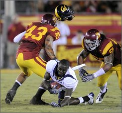 California's wide receiver Nyan Boateng loses his helmet after being hit by Southern California's linebacker Kaluka Maiava, left, and linebacker Rey Maualuga during the first half of a NCAA college football game in Los Angeles, Saturday, Nov. 8, 2008. (AP Photo/Chris Carlson)