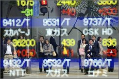 Pedestrians look up at an electric  market board in Tokyo, Monday, Nov. 10, 2008. Japan's key stock index jumped more than 5 percent in early trade Monday as sentiment turned upbeat on China's massive economic stimulus package and a weakening yen. The benchmark Nikkei 225 stock average rose 470.90 points, or 5.49 percent, to close the morning session at 9,053.90. (AP Photo/Katsumi Kasahara)