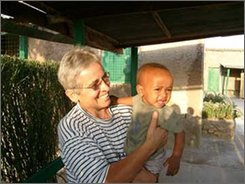 "In this undated picture made available  Monday, Nov. 10, 2008, by the missionary movement  ""Movimento Contemplativo Missionario Padre De  Foucauld"", Italian Roman Catholic nun  Maria Teresa Olivero, is seen with unidentified local child in an unknown location. Gunmen firing automatic weapons dragged Olivero and another Italian Roman Catholic nun Caterina Giraudo (also known as Rinuccia) from their home in rural Kenya on Monday and drove them into lawless Somalia in a rare cross-border attack, officials said. The nuns, who are in their 60s, were working on hunger programs in the northeastern town of El Wak, about six miles (10 kilometers) from the Somali border. The kidnapping highlights concerns among regional security officials that chaos in Somalia could lead to troubles in neighboring Kenya, which is struggling to patrol the long and porous border (AP Photo/  ""Movimento Contemplativo Missionario Padre De  Foucauld"", HO)"