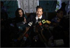 Nicaragua's President Daniel Ortega, right, speaks with journalists after casting his ballot during municipal elections in Managua, Sunday, Nov. 9, 2008. At left, Ortega's wife Rosario Murillo.(AP Photo/Arnulfo Franco)
