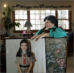 Rosemarie D'Alessandro sits in her home in Hillsdale, N.J., Friday, Nov.  7, 2008, resting her hand on a large portrait of her daughter Joan Angela D'Alessandro who was murdered by a neighbor 35 years ago, when she was seven-years-old. D'Alessandro has been singularly focused on seeking justice for Joan since that horrible day -- April 19, 1973 -- when her daughter was sexually assaulted and fatally strangled while delivering Girl Scout cookies to a neighbor.  (AP Photo/Mel Evans)