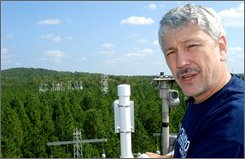 Ram Oren, an associate professor of ecology at Duke University, stands atop an observation tower overlooking the Duke Forest in Durham, N.C., Sept. 29, 2008, where he oversees a long-standing experiment measuring how elevated levels of carbon dioxide expected under global warming will affect forests. The U.S. Department of Energy is changing course on the research, prompting some climate scientists to say an opportunity is being missed to improve the accuracy of climate change models. (AP Photo/Jeff Barnard)