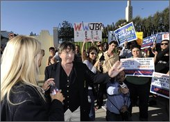"Robin Tyler, center, addresses protesters as Diane Olson looks on in this Nov. 6, 2008 file photo during a ""No on Prop 8"" march and rally in front of the Mormon Church to protest the church's monetary support of Prop 8 in Los Angeles. California's gay-rights movement has been beset by infighting and finger-pointing since the defeat of gay marriage at the ballot box, with some activists questioning the campaign's mild tactics, including the decision not to show same-sex couples in ads. The movement's leaders ""were very timid. They were too soft,"" said Robin Tyler, a lesbian comic who created a series of celebrity public service announcements with the slogan ""Stop the Hate, No on 8"" that were rejected because they were deemed too negative. ""We were lightweights on our side.""(AP Photo/Kevork Djansezian, File)"