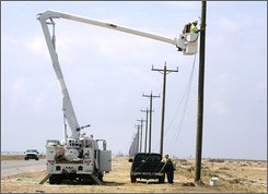 In this Oct. 10, 2008 file photo, utilities workers from Joplin, Mo. begin to string power lines on new poles along the coastal highway on Bolivar Peninsula near Gilchrist, Texas, nearly a month after Hurricane Ike wiped out the homes on this sliver of land just north of Galveston. Full restoration of power and water to the peninsula probably won't be completed until mid-to-late November. (AP Photo/Pat Sullivan, File)