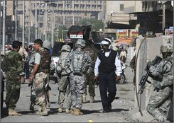 U.S. troops and Iraqi security forces inspect the site where a roadside bomb injured two electricians in central Baghdad, Iraq on Tuesday, Nov. 11, 2008. (AP Photo/Hadi Mizban)
