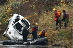 Divers remove a car submerged in the Green River on Tuesday afternoon, Nov. 11, 2008, but found only the body of a 2-year-old boy inside. A 13-year-old boy who was also in the car Friday when it plunged into the river is still missing, and crews from the King County Sheriff's Office searched for his body until nightfall. The 2-year-old was found still strapped into his car seat. (AP Photo/Seattle Post-Intelligencer, Mike Kane)