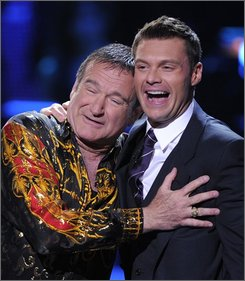 "In this April 6, 2008 file photo, Robin Williams, left, and Ryan Seacrest embrace on stage at the ""Idol Gives Back"" fundraising special of ""American Idol"" in Los Angeles. (AP Photo/Mark J. Terrill, file)"