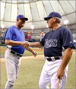 In this June 17, 2008 file photo, Chicago Cubs manager Lou Piniella, left, meets with Tampa Bay Rays manager Joe Maddon prior to a baseball game Tuesday, June 17, 2008, in St. Petersburg, Fla.  Maddon won the American League Manager of the Year award Wednesday Nov. 12, 2008. Piniella  is the National League winner.(AP Photo/Mike Carlson, File)