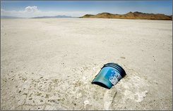 In this July 17, 2007 file photo, a plastic bucket lies half buried in the dried out bed of the Great Salt Lake, northwest of Salt Lake City. All summer and into the fall of 2008, warm temperatures kept evaporation humming, drawing down the lake to near-record low levels and exposing more shore than normal. But the shrinking appears finally to have stopped.  (AP Photo/Douglas C. Pizac, File)
