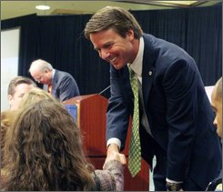 Two-time presidential candidate John Edwards, foreground, and former White House Chief of Staff Karl Rove, background, interact with the audience after a post-election discussion at the Commercial Finance Association's 64th Annual Convention, Thursday, Nov. 13, 2008 in San Francisco. (AP Photo/George Nikitin)