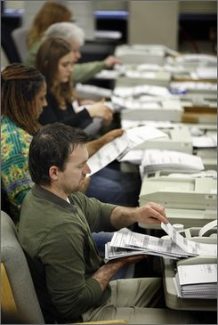 Election workers run ballots through scanners as they count absentee and early vote ballots at the Division of Elections office in Anchorage, Alaska Wednesday Nov. 12, 2008. About 90,000 votes are outstanding in a close U.S. Senate and House race. (AP Photo/Al Grillo