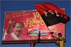 A supporter of Nicaragua's Sandinista National Liberation Front, FSLN, waves a partisan flag next to a billboard with the image of  Nicaragua's President Daniel Ortega in Managua, Thursday, Nov. 13, 2008.  Nicaragua's election council has agreed to allow a review of the capital's mayoral election results after opponents of Ortega cried fraud. (AP Photo/Esteban Felix)