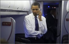 President-elect Obama talks on his cell phone after boarding his plane at Washington's Reagan National Airport after meeting with President Bush at the White House in Washington, Monday, Nov. 10, 2008. (AP Photo/Charles Dharapak)