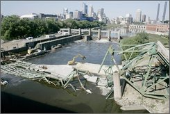 In this Aug. 31, 2007 file photo, the Minneapolis skyline is shown in the distance in this view of the Interstate 35W bridge which collapsed into the Mississippi River, Aug. 1, into the Mississippi River in Minneapolis. Transportation safety officials are set to issue a final ruling this week on the cause of the deadly Minneapolis bridge collapse that killed 13 people and injured 145. (AP Photo/Jim Mone,file)
