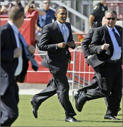 In this Oct. 30, 2008 file photo, then-Democratic presidential candidate Sen. Barack Obama, D-Ill. runs with U.S. Secret Service agents as he enters a rally at Ed Smith Stadium in Sarasota, Fla. President-elect Barack Obama -- aka Renegade -- had a say in choosing the code name that his protectors use when they're whispering into those microphones in their sleeves. (AP Photo/Alex Brandon, File)