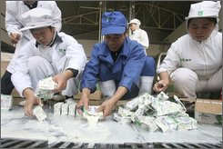 Workers squeeze melamine-tainted milk into a drainage ditch leading to the sewage treatment plant at a Mengniu Dairy factory in Wuhan in central China's Hubei province Wednesday, Nov. 5, 2008. Now that the worst of China's tainted dairy scandal appears to be over, authorities are tackling the next problem