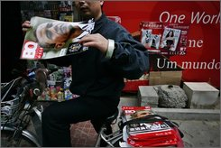 A newspaper and magazine delivery man picks up copies of a magazine displaying U.S. President-elect Barack Obama on its cover at a news stand in Beijing , China, Friday, Nov. 14, 2008. (AP Photo/ Elizabeth Dalziel)