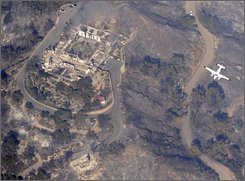 Mount Calvary Benedictine Monastery, left, appears destroyed as a fire fighting spotter aircraft flies past after a wind-driven wildfire swept through Montecito, Calif., near Santa Barbara, Friday, Nov. 14, 2008. (AP Photo/Kevork Djansezian)