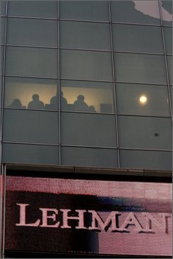 """In this Monday, Sept. 15, 2008 file photo, office workers are seen through a window silhouetted against a wall of the Lehman Brothers headquarters in New York. A reader-submitted question about Lehman Brothers bondsl is being answered as part of an Associated Press Q&A column called """"Ask AP"""". (AP Photo/Mary Altaffer/file )"""
