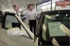 Chevrolet sales manager Tom Callahan, left, shows Edward Dollard a 2008 Cadillac DTS Wednesday, Nov. 12, 2008, in downtown Los Angeles. Retail sales plunged by the largest amount on record in October as the financial crisis and the slumping economy caused consumers to sharply cut back on their spending. (AP Photo/Ric Francis)