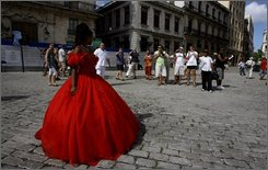 A young woman celebrating her 15th birthday posses for tourists in Old Havana, Friday, Nov. 14, 2008. According to authorities around two million tourists have visited Cuba in the last twelve months. (AP Photo/Javier Galeano)