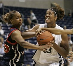Xavier center Ta'Shia Phillips, right, is fouled as she shoots against Robert Morris forward Grace Williams, left, during the first half of an NCAA women's college basketball game, Friday, Nov. 14, 2008, in Cincinnati. (AP Photo/Al Behrman)