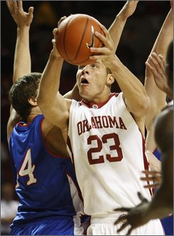 Oklahoma center Blake Griffin, right, goes up for a shot in front of American forward Brian Gilmore, left, during the first half of an NCAA men's college basketball game in Norman, Okla., Friday, Nov. 14, 2008. (AP Photo/Sue Ogrocki)