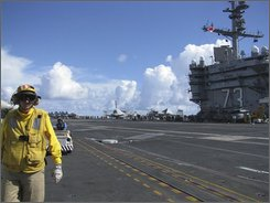 A deck crew walks by the landing strip on the deck of the USS George Washington in the western Pacific Monday, Oct. 20, 2008. The George Washington, the crown jewel of the U.S. 7th Fleet, is a floating air base with 67 aircraft ready to fly; it is city unto itself, with a population of around 5,000; and it is an armory of mind-boggling proportion, carrying somewhere around 4 million pounds of bombs. (AP Photo/Eric Talmadge)
