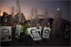 People hold banners depicting six Jesuit priests massacred in 1989, during an act to commemorate the 19 th anniversary of their death in San Salvador, Saturday, Nov. 15, 2008. Thursday Human Rights groups asked a Spanish court to indict former Salvadoran President Alfredo Cristiani Burkard and 14 ex-officials over the massacre of the six priests, their housekeeper and her teenage daughter.(AP Photo Edgar Romero)