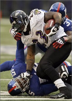 New York Giants cornerback Aaron Ross, right, intercepts a pass intended for Baltimore Ravens wide receiver Derrick Mason, left, during the first half of an NFL football game, Sunday, Nov. 16, 2008, in East Rutherford, N.J. (AP Photo/Rob Carr)