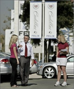 "Chevrolet salesman Philip Jordan, center, assists Charlotte Olson, right, who's looking to buy a car for her 18-year-old daughter, Kari Olson, left, Wednesday, Nov. 12, 2008, in downtown Los Angeles. Treasury Secretary Henry Paulson called autos a ""critical industry"" Wednesday but said a $700 billion financial rescue program wasn't designed for them. The White House was noncommital, but said it was open to new ideas. (AP Photo/Ric Francis)"
