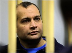 Sergei Khadzhikurbanov, a former Moscow police officer, sits behind bars at a court room in Moscow on Monday, Nov. 17, 2008. The suspects being tried on murder charges are Sergei Khadzhikurbanov -- a former Moscow police officer -- and Makhmudov's brothers, Ibragim and Dzhabrail. A Russian court ruled Monday that the trial of three men accused of involvement in the slaying of journalist Anna Politkovskaya should be open to the public. (AP Photo/ Sergey Ponomarev)